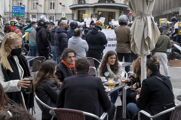 People sit around a table in a sidewalk bar as delivery riders protest behind them outside the Spanish parliament in Madrid, Wednesday March 3, 2021. TFood delivery workers have staged protests across Spain, urging the government to approve a promised law granting them the right to choose between being company staff or self-employed. Media reports said more than 2,000 delivery riders gathered to protest in at least 10 Spanish cities on Wednesday. (AP Photo/Paul White)
