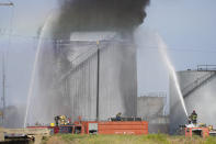 Firefighters work to extinguish a fire in an oil facility in the southern town of Zahrani, south of the port city of Sidon, Lebanon, Monday, Oct. 11, 2021. A huge fire broke out at an oil facility in southern Lebanon's coastal town of Zahrani, but the cause was not immediately known. (AP Photo/Hassan Ammar)