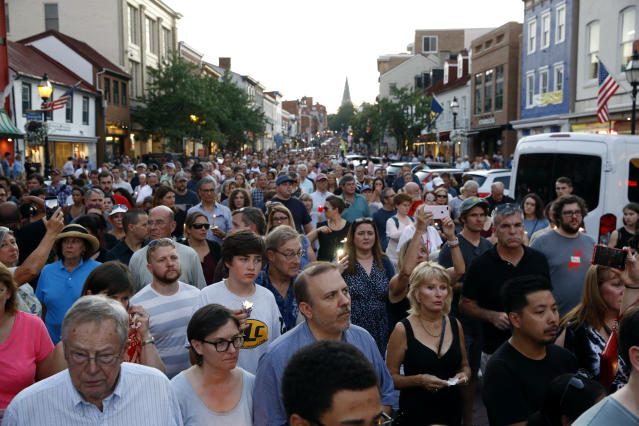 <p>Mourners walk during a vigil in response to a shooting at The Capital Gazette newspaper office, Friday, June 29, 2018, in Annapolis, Md. The suspect, Jarrod W. Ramos, is charged with five counts of first-degree murder in one of the deadliest attacks on journalists in U.S. history. (Photo: Patrick Semansky/AP) </p>