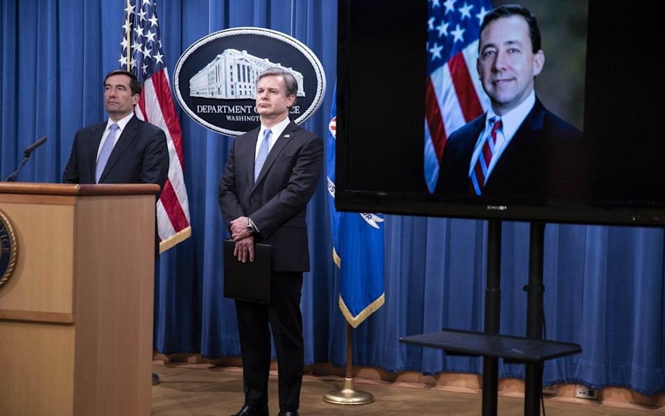 Assistant attorney general for national security John C Demers (left), FBI director Christopher Wray and acting US attorney for the Eastern District of New York Seth DuCharme (on screen) announce the charges at the Department of Justice - Shutterstock