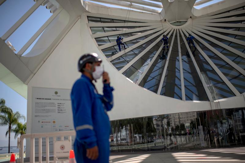 Workers disinfect an area of the Museum of Tomorrow prior to its reopening in Rio de Janeiro, Brazil on September 4, 2020, amid the COVID-19 novel coronavirus pandemic. - India, the United States and Brazil remain the three countries recording the greatest number of new cases over the past seven days, with 77,596, 40,875 and 40,035 cases respectively per day on average, according to an AFP count on Friday at 1100GMT. (Photo by MAURO PIMENTEL / AFP) (Photo by MAURO PIMENTEL/AFP via Getty Images)