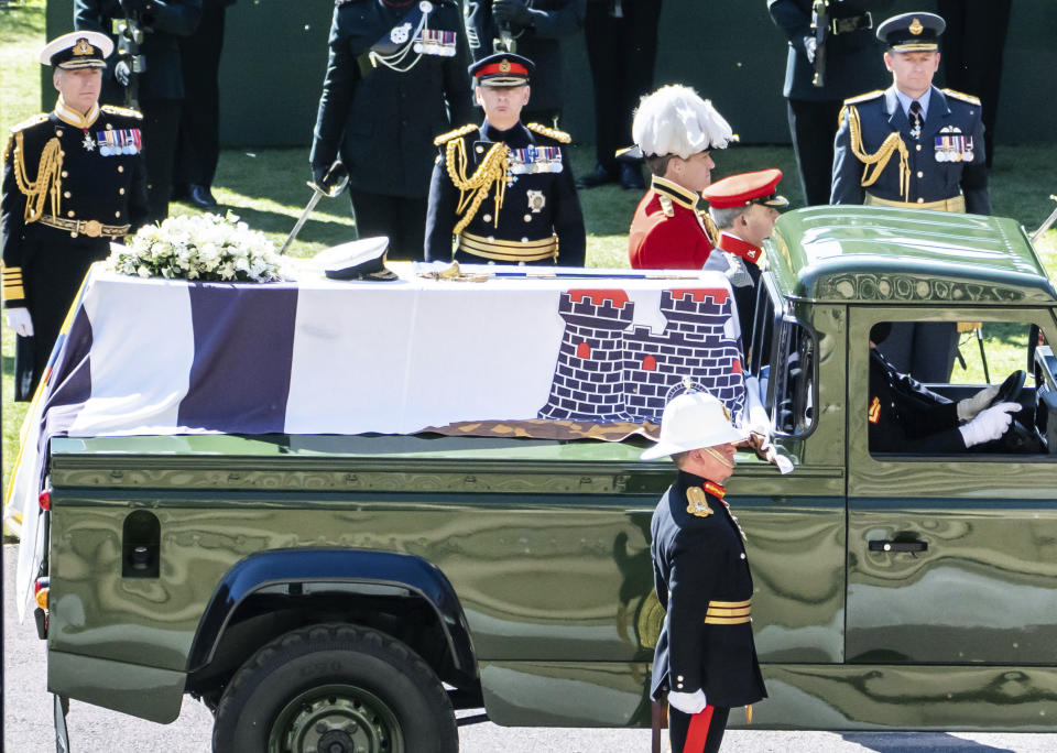 The Duke of Edinburgh's coffin, covered with his Personal Standard, is carried on the purpose built Land Rover Defender ahead of his funeral, at St George's Chapel, Windsor Castle, in Windsor, England, Saturday April 17, 2021. Prince Philip died April 9 at the age of 99 after 73 years of marriage to Britain's Queen Elizabeth II. (Danny Lawson/Pool via AP)