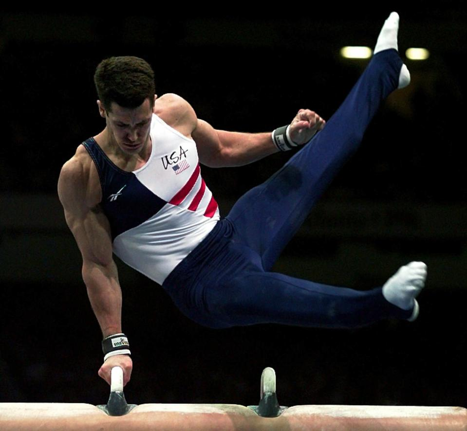 FILE - Team USA's John Roethlisberger performs his routine on the pommel horse during the men's all around competition at the Centennial Summer Olympic Games in Atlanta, in this Wednesday, July 24, 1996, file photo. The cutback in NCAA athletic programs due to the COVID-19 pandemic is being felt acutely in men's gymnastics. For decades Division I programs have produced an overwhelming majority of the US Olympic team. The number of Division I programs, however, is shrinking. The University of Minnesota and the University of Iowa will stop offering it as a scholarship sport at the end of the month. That will drop the number of Division I schools to 11. (AP Photo/Joe Cavaretta, File)