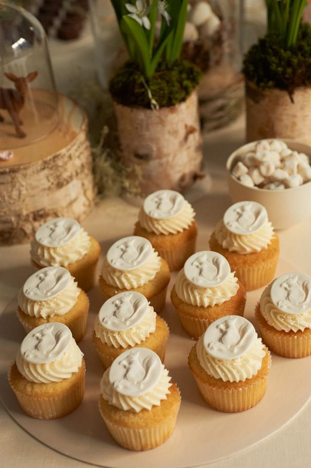 """<p>""""Bring a bit of the outdoors in for your tablescape. Incorporate woodland creatures, like squirrels and deer, into the smaller details for a bit of surprise and delight, like I have here on these cupcakes as seen in my book, <em>Celebrate Everything!</em>.<em> </em>Mix in flora and fauna with a variety of white flowers. You can use unique vessels, like these birch rounds, to play up the nature theme."""" — <a href=""""http://www.darcymillerdesigns.com/"""" target=""""_blank"""">Darcy Miller</a>, Author and Entertaining Expert</p>"""