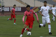 South Korea's Hwang Ui Jo, center, tries to pass from Iran's Saeid Ezatolahi during their final round of the Asian zone qualifying soccer match for the FIFA World Cup Qatar 2022 at Azadi Stadium in Tehran, Iran, Tuesday, Oct. 12, 2021. (AP Photo/Vahid Salemi)
