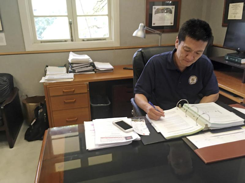 In this Friday, March 10, 2017 photo, Hawaii Attorney General Douglas Chin works in his office in Honolulu. Hawaii was the first state to file a lawsuit challenging President Donald Trump's revised travel ban. For Chin, the son of Chinese immigrants, fighting the travel ban is personal. (AP Photo/Jennifer Sinco Kelleher).
