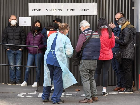 A medical worker speaks to people queueing outside a COVID-19 coronavirus testing venue at The Royal Melbourne Hospital.