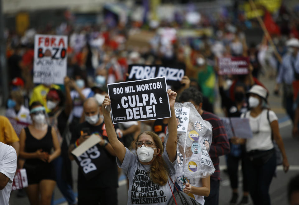 """A woman wearing a protective face mask holds a sign with a message that reads in Portuguese; """"500 k deaths! His fault!"""" during a protest against Brazilian President Jair Bolsonaro's handling of the coronavirus pandemic and economic policies they say harm the interests of the poor and working class, in Rio de Janeiro, Brazil, Saturday, June 19, 2021. Brazil is approaching an official COVID-19 death toll of 500,000 — second-highest in the world. (AP Photo/Bruna Prado)"""
