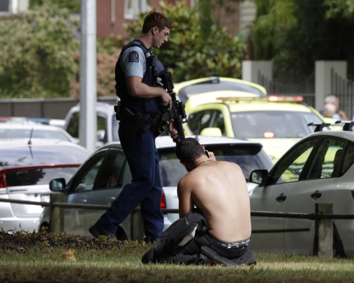 <p>A man rests on the ground as he speaks on his mobile phone across the road from mosque in central Christchurch, New Zealand. (AP Photo/Mark Baker) </p>