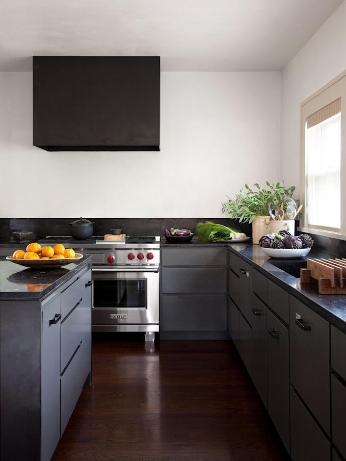 In keeping with Tedhams's reliance on a limited palette, the kitchen cabinets are painted the same color as the exterior of the house. Countertops are Belgian bluestone. Range by Wolf; dishwasher by Fisher & Paykel.