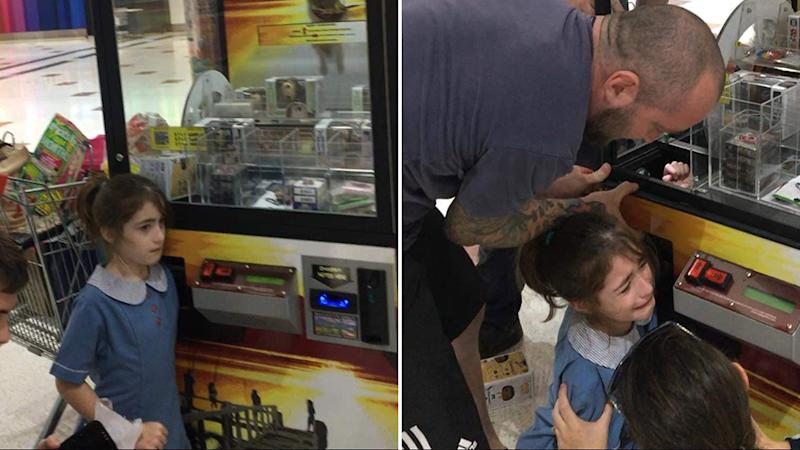 Martin Kristoffersen is pictured on the right trying to free his distressed daughter, Hannah (left), from a skill tester at Wynnum Plaza.
