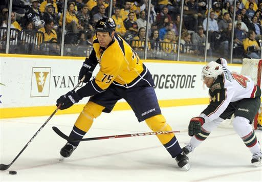 Nashville Predators defenseman Hal Gill (75) keeps the puck from Minnesota Wild right wing Jed Ortmeyer (41) during the first period of an NHL hockey game on Tuesday, April 3, 2012, in Nashville, Tenn. (AP Photo/Mike Strasinger)