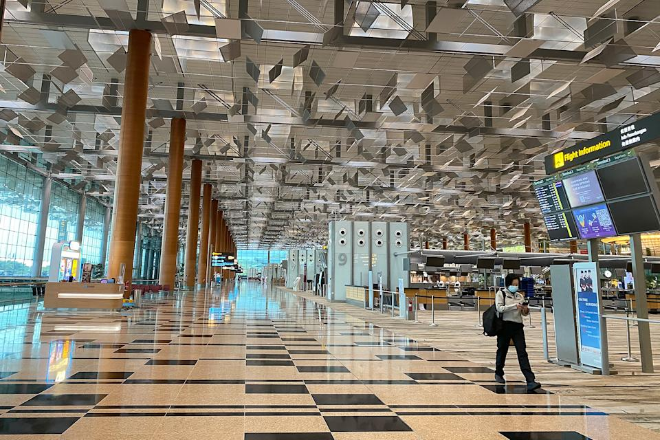 An airport worker seen walking past the empty check-in rows at Changi Airport's Terminal 3 on 11 October 2020. (PHOTO: Dhany Osman / Yahoo News Singapore)
