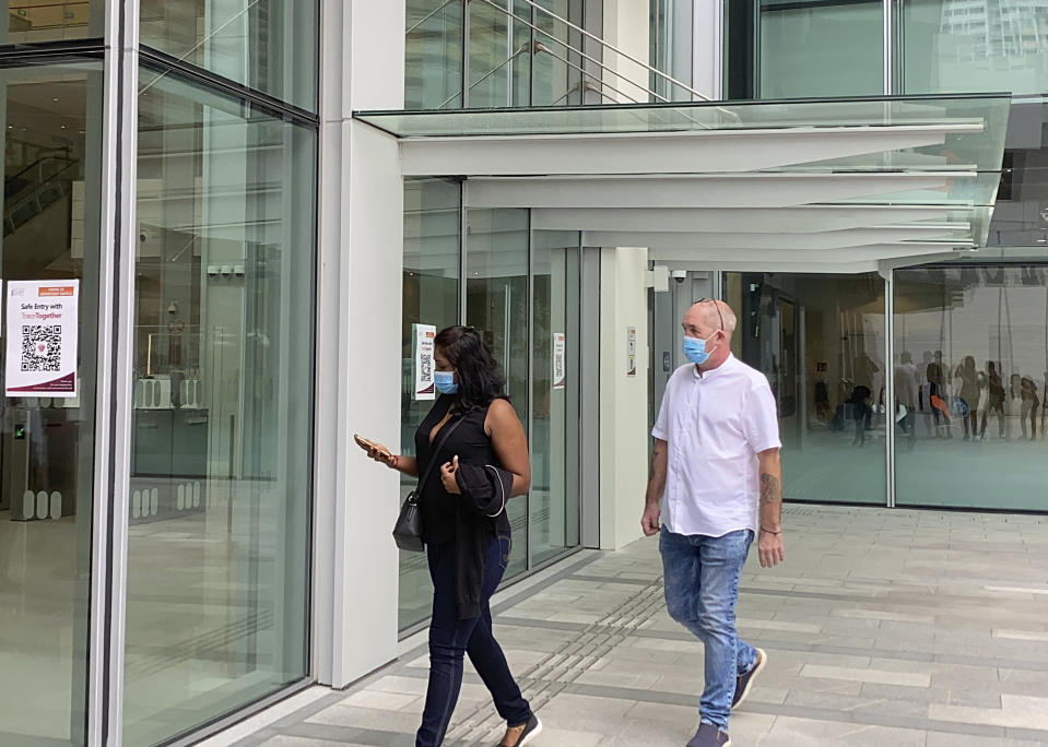 Agatha Maghesh Eyamalai, left, and Skea Nigel walk into the State Courts in Singapore, Monday, Feb. 15, 2021. The Briton man pleaded guilty on Monday to violating a coronavirus quarantine order in Singapore to visit his fiancee. (AP Photo/Annabelle Liang)