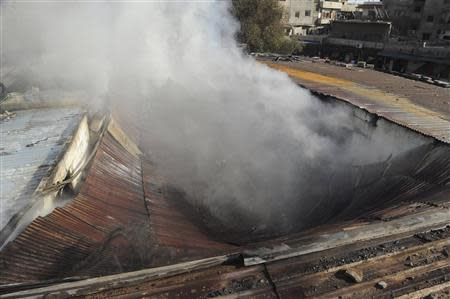 A view shows smoke rising after a mortar shell hit a textile factory at al-Dweil'a neighbourhood in Damascus on Sunday November 3, 2013, causing a huge fire in the factory, but no one was hurt, state media said, in this handout released by Syria's national news agency SANA. REUTERS/SANA/Handout via Reuters