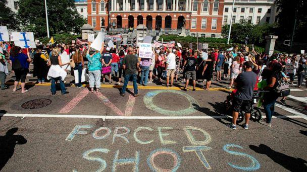 PHOTO: People draw a 'No Forced Shots' message on the street in chalk during a protest after a mandate requiring all children,age K-12, to receive an influenza (flu) vaccine/shot to attend school in Boston on August 30, 2020. (Joseph Prezioso/AFP via Getty Images)