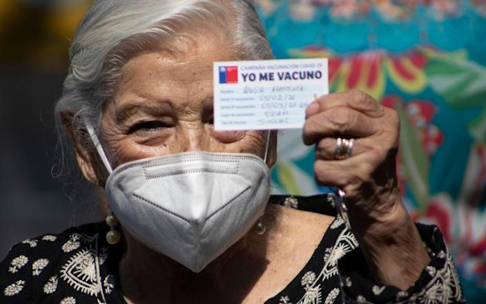 Alicia Martinez holds up her vaccination card after she was injected with a second dose of China's Sinovac COVID-19 vaccine - Esteban Felix/AP Photo