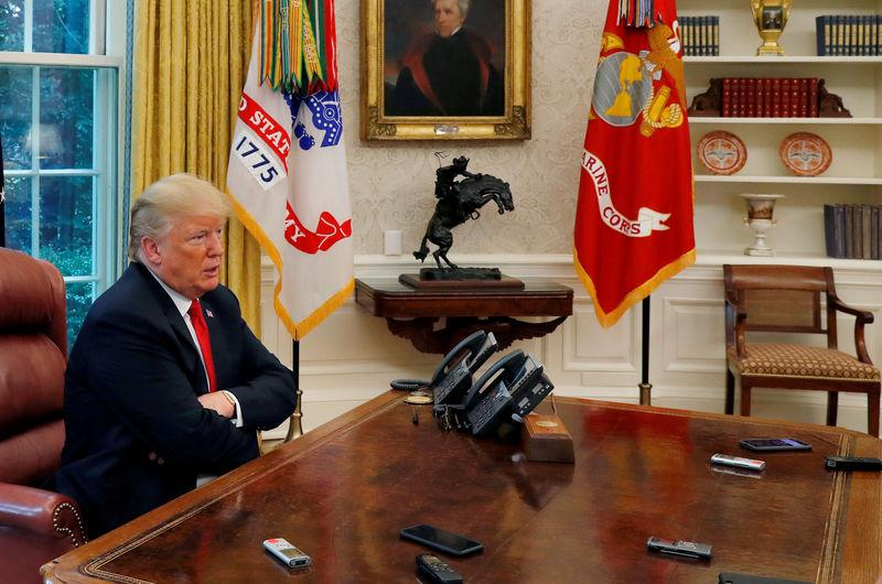 U.S. President Donald Trump answers a reporter's question as eight different phones and recording devices placed on his desk by reporters and White House staff members record his words during an interview with Reuters in the Oval Office of the White House in Washington, U.S. August 20, 2018. REUTERS/Leah Millis