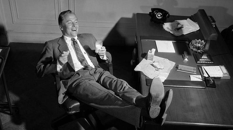 Black and white photo of man laughing with feet up on desk, drinking glass of milk
