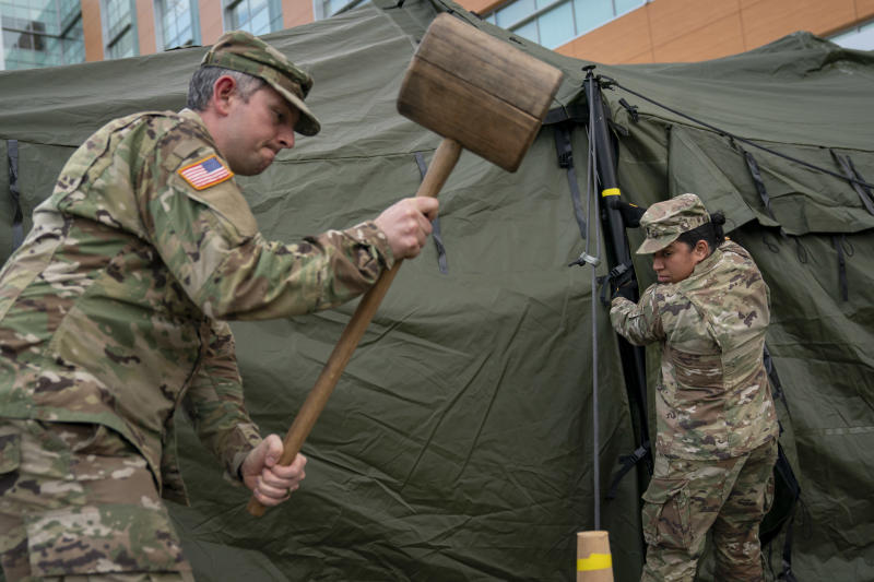 SILVER SPRING, MD - MARCH 19: Members of the Maryland Army National Guard work to set up a triage tent in the parking lot outside of the emergency room at Adventist HealthCare White Oak Medical Center on March 19, 2020 in Silver Spring, Maryland. Hospitals across the country are preparing for an influx of additional patients due to the COVID-19 pandemic. (Photo by Drew Angerer/Getty Images)