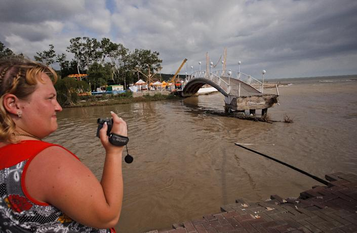 A woman takes video of the flood in the Black Sea resort of Gelendzhik, southern Russia, Saturday, July 7, 2012. Intense flooding in the Black Sea region of southern Russia killed 103 people after torrential rains dropped nearly a foot of water, forcing many to scramble out of their beds for refuge in trees and on roofs, officials said Saturday. (AP Photo/Ignat Kozlov)