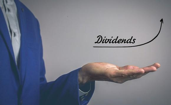 Man's hand, palm up, with an upward arrow and the word dividends above it.