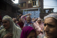 Kashmiri woman shout freedom slogans near the body of Bashir Ahmad, a civilian killed in a shootout, during his funeral at Sopore, 55 kilometers (34 miles) north of Srinagar, Indian controlled Kashmir, Saturday, June 12, 2021. Two civilians and two police officials were killed in an armed clash in Indian-controlled Kashmir on Saturday, police said, triggering anti-India protests who accused the police of targeting the civilians. (AP Photo/Mukhtar Khan)