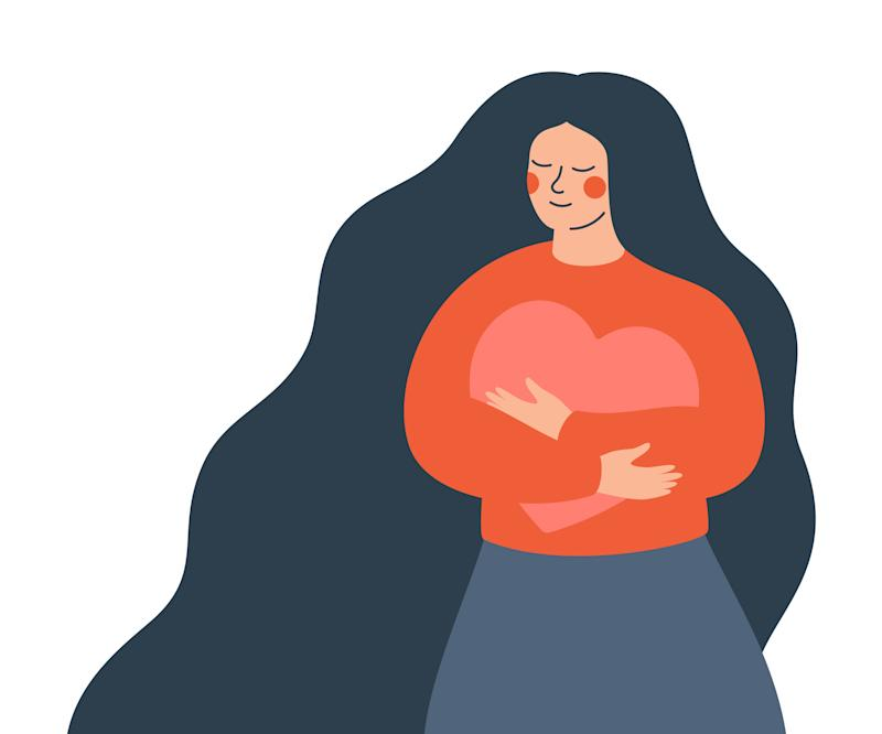 Young woman hugs a big heart with love and care. Girl with long hair holds pink heart in her hands. Self care and body positive concept.