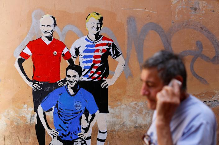 """<p>A man walks past a mural signed by """"TV Boy"""" and depicting Russian President Vladimir Putin, U.S. President Donald Trump and Italian Prime Minister Giuseppe Conte as soccer players in downtown Rome, Italy June 15, 2018. (Photo: Tony Gentile/Reuters) </p>"""
