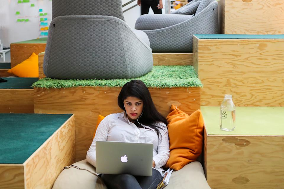 A woman works at her Apple computer at the Airbnb office headquarters in the SOMA district of San Francisco, California, U.S., August 2, 2016.   REUTERS/Gabrielle Lurie