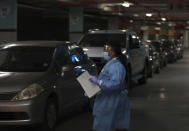 A health-care worker directs vehicles as patients queue for COVID-19 testing at a Dis-Chem drive-through testing station at the Table Bay Mall in Cape Town, South Africa, Friday, Jan. 8, 2021. South Africa with 60 million people has reported by far the most cases of the coronavirus in Africa, with more than 1.1 million confirmed infections. (AP Photo/Nardus Engelbrecht)