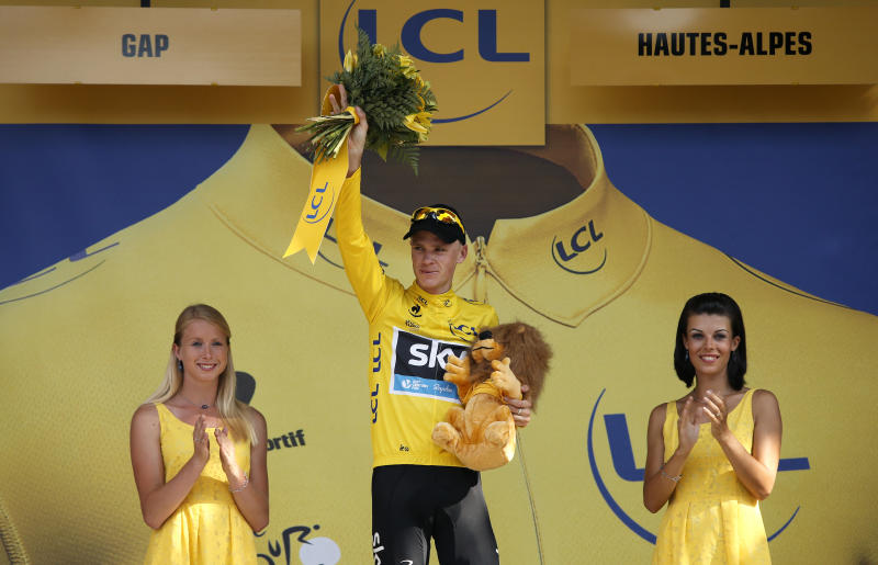 Christopher Froome of Britain, wearing the overall leader's yellow jersey, celebrates on the podium of the sixteenth stage of the Tour de France cycling race over 168 kilometers (105 miles) with start in in Vaison-la-Romaine and finish in Gap, France, Tuesday July 16, 2013. (AP Photo/Laurent Cipriani)