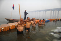 Devotees pray and take holy dips at Sangam, during Magh Mela festival, in Prayagraj, India. Friday, Feb. 19, 2021. Millions of people have joined a 45-day long Hindu bathing festival in this northern Indian city, where devotees take a holy dip at Sangam, the sacred confluence of the rivers Ganga, Yamuna and the mythical Saraswati. Here, they bathe on certain days considered to be auspicious in the belief that they be cleansed of all sins. (AP Photo/Rajesh Kumar Singh)