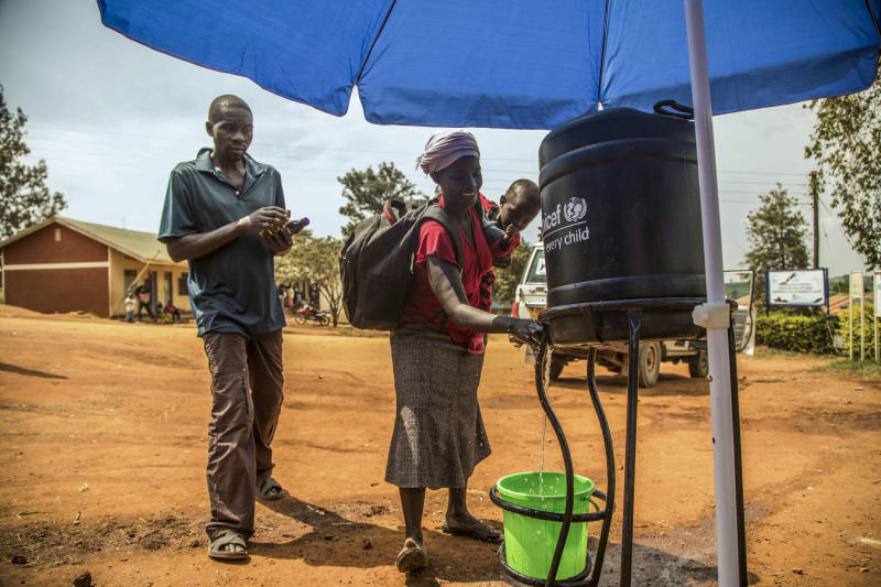 In this photo provided by the International Rescue Committee, Congolese refugees wash their hands before being screened for Ebola symptoms at the IRC triage facility in the Kyaka II refugee settlement in Kyegegwa District in western Uganda, Thursday, June 13, 2019. The Congolese pastor who is thought to have caused the Ebola outbreak's spread into Uganda was unknown to health officials before he died of the disease, the World Health Organization's emergencies chief said Thursday, underlining the problems in tracking the virus. (Kellie Ryan/International Rescue Committee via AP)