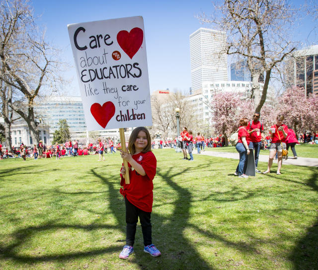 <p>Emeila Coleman, 6, of Colorado Springs, Colo., holds a sign that is roughly the same size as she is as she and thousands of teachers and supporters rally in Civic Center Park in Denver, Colo., on Friday, April 27, 2018. (Photo: Dougal Brownlie/The Gazette via AP) </p>