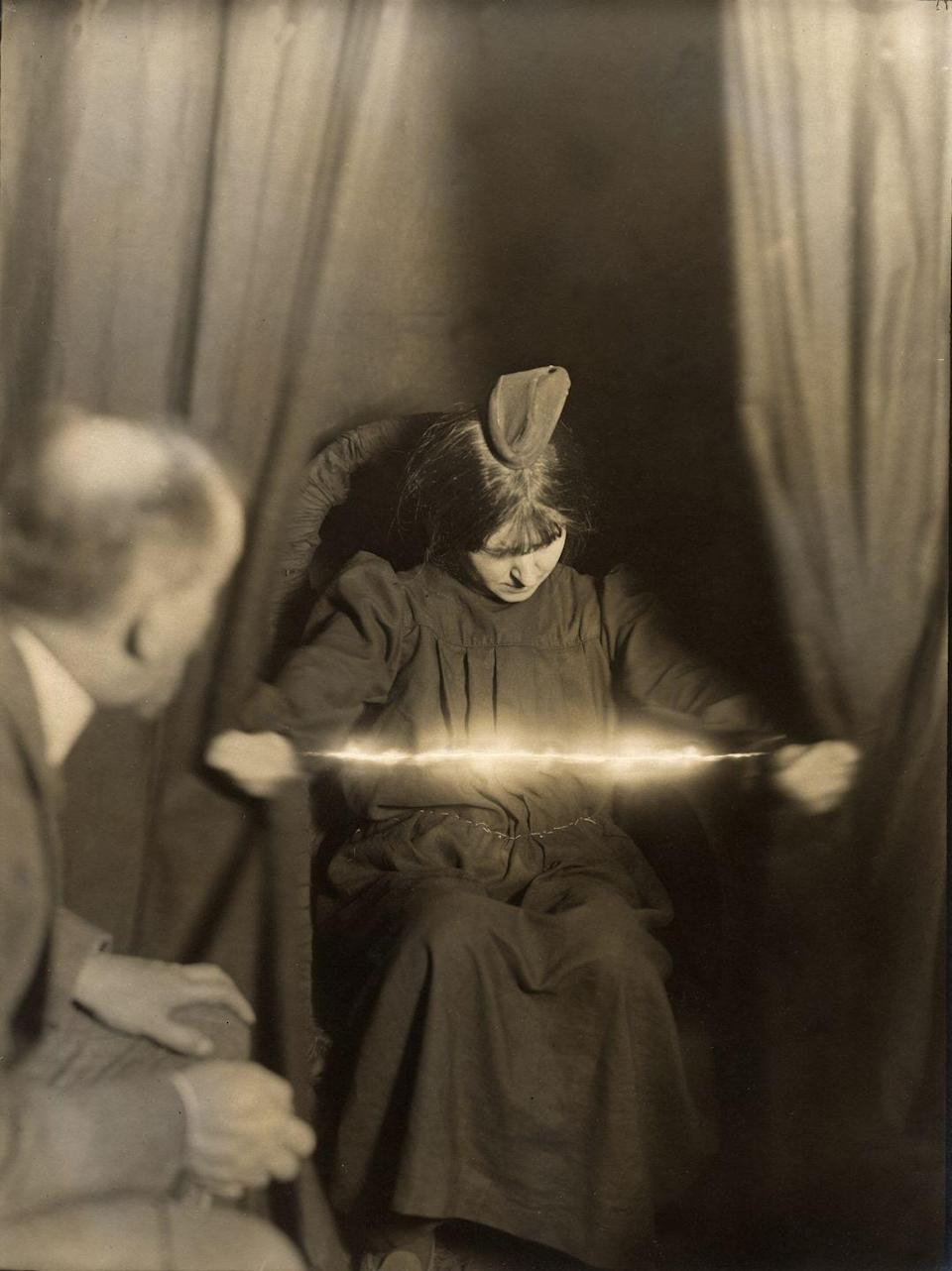 """<p>A spiritual medium, Eva Carriere, holds a glowing rod with both of her hands during a spiritual seance. According to the book <em>A Magician Among the Spirits</em>, at the turn of the 20th century, <a href=""""https://www.cambridge.org/core/books/magician-among-the-spirits/287B6F1D1986740CAC42E55B1D60792C"""" rel=""""nofollow noopener"""" target=""""_blank"""" data-ylk=""""slk:Carriere was a popular medium who was even observed by magician Harry Houdini"""" class=""""link rapid-noclick-resp"""">Carriere was a popular medium who was even observed by magician Harry Houdini</a>, in an attempt to pick up a few of her tricks.</p>"""