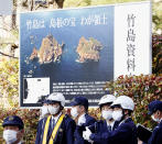 """Police officers stand guard near the venue of a ceremony to mark Shimane Prefecture-designated """"Takeshima Day"""" in Matsue, Shimane prefecture, western Japan, Monday, Feb. 22, 2021. Japan renewed its claim on a contested island in the Sea of Japan held by South Korea at an annual event Monday, escalating tensions between the neighbors were already strained over Seoul's compensation claim over Tokyo's World War II atrocities. The island is called """"Takeshima"""" in Japan and """"Dokdo"""" in South Korea. The poster in the background reads: """"Takeshima is Shimane's treasure, my territory."""" (Kyodo News via AP)"""