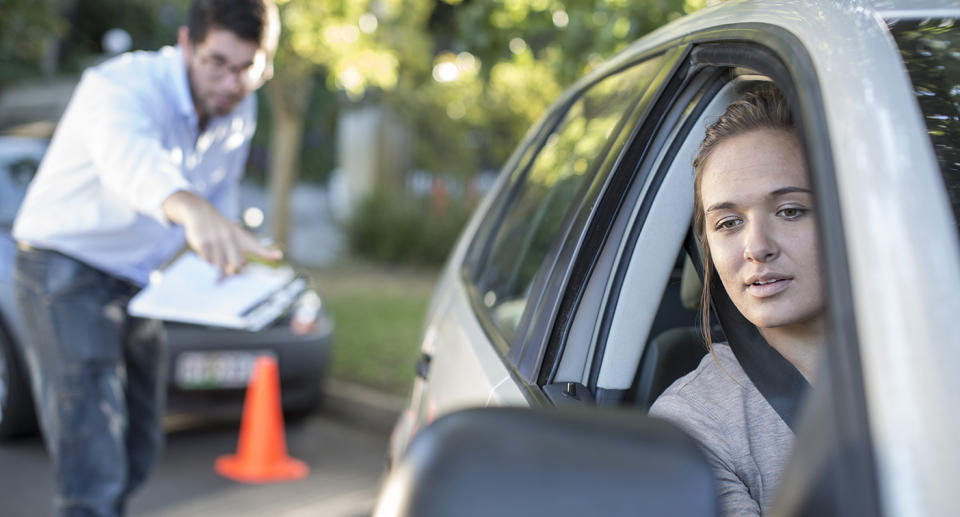 Young woman reverse parking as a man instructs her. Source: Getty Images