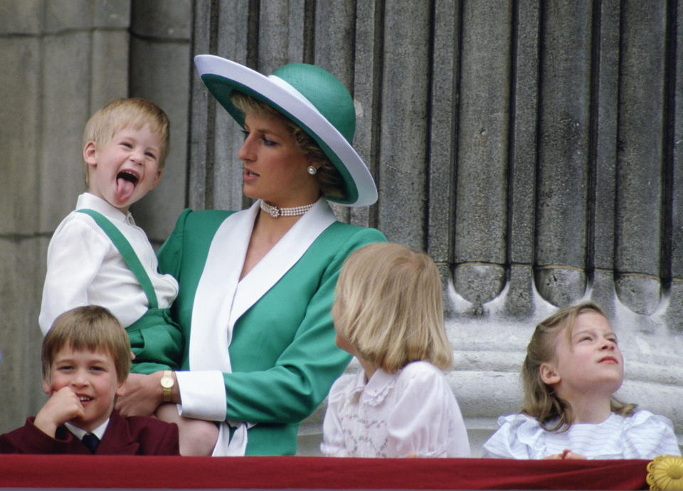 Prince Harry sticks out his tongue, much to the surprise of his mother Princess Diana, as Prince William, Lady Gabriella Windsor And Lady Rose Windsor watch the flypast. (PA Images)