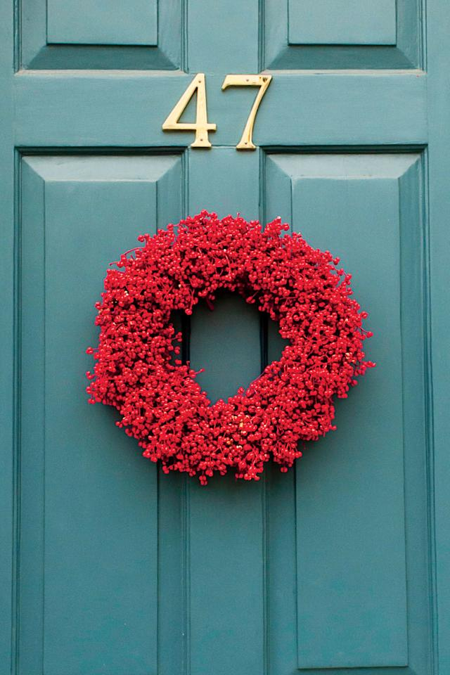 <p>A bold shade of red instantly brings Christmas cheer to any front door. This simply stated version adds the perfect festive touch.</p>