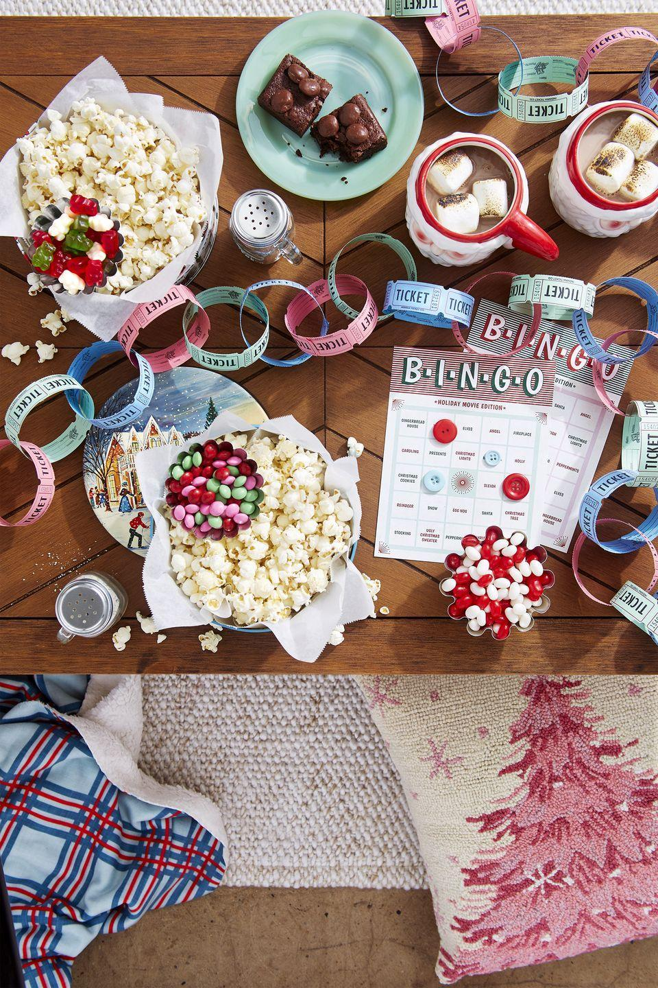 """<p>Build a fire, curl up with your family and friends, and get in the spirit of Christmas with your <a href=""""https://www.countryliving.com/life/entertainment/g5034/top-christmas-movies/"""" rel=""""nofollow noopener"""" target=""""_blank"""" data-ylk=""""slk:favorite holiday classics"""" class=""""link rapid-noclick-resp"""">favorite holiday classics</a>, like <em>The Polar Express</em>, <em>Home Alone</em>, and <em>Miracle on 34th Street</em>. Serve fresh popcorn with optional popcorn seasonings like parmesan black pepper, cinnamon sugar, or everything bagel for a holiday treat. Don't forget the toasted marshmallow hot cocoa and the theatre candy brownies. To make things extra fun, ask guests to play <a href=""""https://www.countryliving.com/life/entertainment/a34555161/christmas-bingo/"""" rel=""""nofollow noopener"""" target=""""_blank"""" data-ylk=""""slk:Binge-Watch Bingo"""" class=""""link rapid-noclick-resp"""">Binge-Watch Bingo</a> using buttons or popcorn to mark the squares.</p>"""