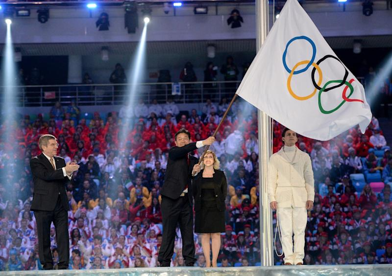 International Olympic Committee President Thomas Bach, left, applauds as Lee Seok-rai, mayor of Pyeongchang, waves the Olympic flag during the closing ceremony of the 2014 Winter Olympics, Sunday, Feb. 23, 2014, in Sochi, Russia. (AP Photo/Jung Yeon-je, Pool)