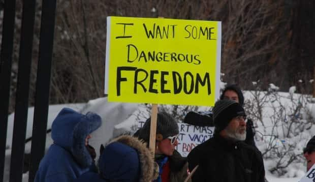 A protester holds a sign reading 'I want some dangerous freedom' at the demonstration in Whitehorse Friday. (Philippe Morin/CBC - image credit)