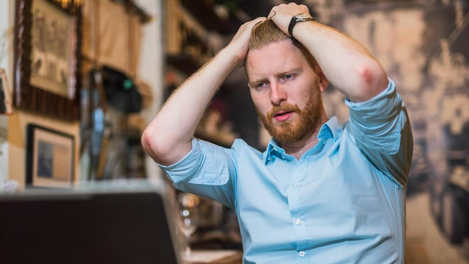 frustrated man looking at stocks tanking on his laptop