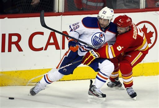 Edmonton Oilers' Sam Gagner, left, battles Calgary Flames' Mark Giordano for the puck during the third period of NHL hockey game in Calgary, Alberta, Saturday, Jan. 26, 2013. The Flames won 4-3. (AP Photo/The Canadian Press, Jeff McIntosh)