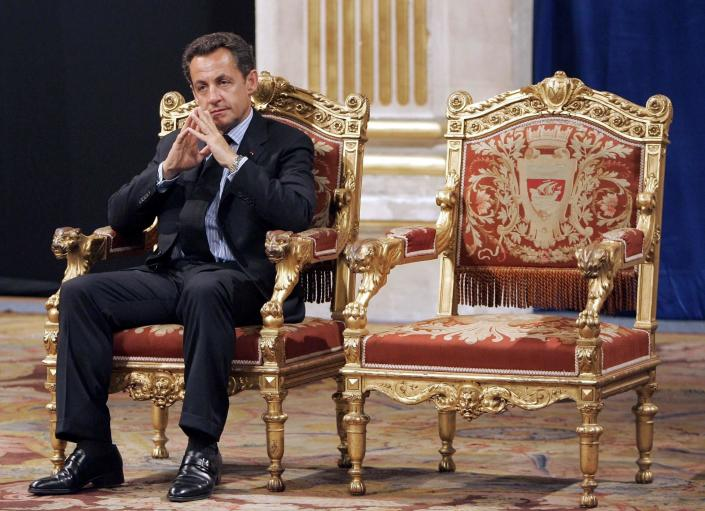 FILE - In this Thursday, May, 24, 2007 file photo, French President Nicolas Sarkozy sits during an official and traditional ceremony with Paris mayor Bertrand Delanoe, whose empty chair is at right, during which the newly elected President is met by the Paris mayor at the Paris city hall, France. A Paris court on Monday found French former President Nicolas Sarkozy guilty of corruption and influence peddling and sentenced him to one year in prison and a two-year suspended sentence. The 66-year-old politician, who was president from 2007 to 2012, was convicted for having tried to illegally obtain information from a senior magistrate in 2014 about a legal action in which he was involved. (AP Photo/Christophe Ena, File)