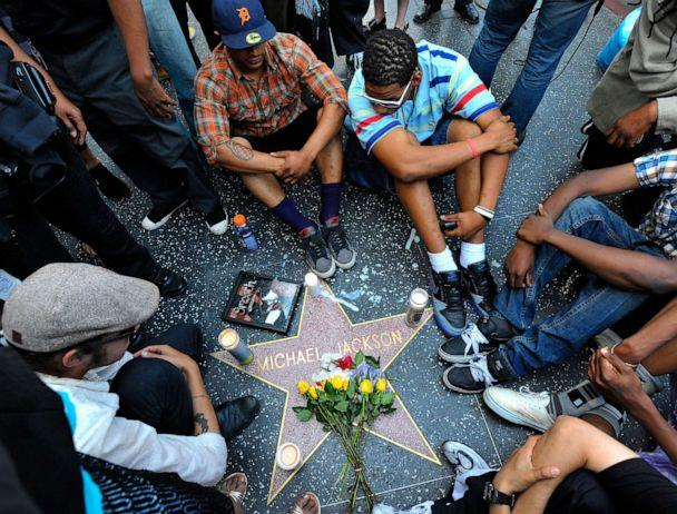 PHOTO: Fans of pop star Michael Jackson sit vigil at talk radio host Michael Jackson's Star on the Hollywood Walk of Fame mourning his death on June 25, 2009 in Los Angeles, California. (Charley Gallay/Getty Images)