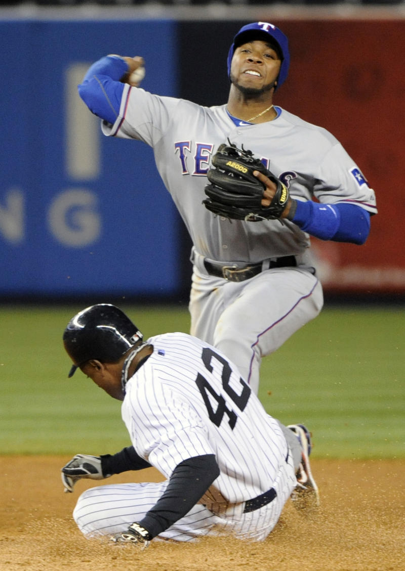 New York Yankees' Curtis Granderson, bottom, is out at second base as Texas Rangers shortstop Elvis Andrus, top, relays the ball to first to complete the double play on Derek Jeter during the fifth inning of a baseball game on Friday, April 15, 2011, at Yankee Stadium in New York. The Rangers won 5-3. (AP Photo/Bill Kostroun)