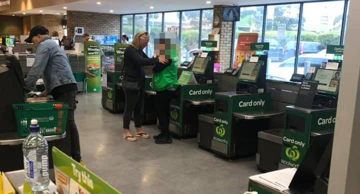 A Woolworths staff member is pictured crying at the self-checkout.