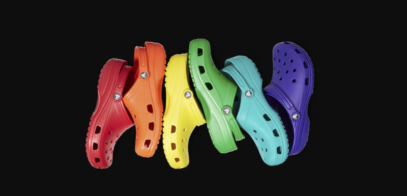 Six Crocs shoes in the colors of the rainbow.